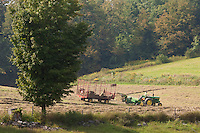 A farmer uses a tractor and a kick baler in a farm in Madison County, NY, Wednesday September 11, 2013. A baler is a piece of farm machinery used to compress a cut and raked crop into compact bales that are easy to handle, transport, and store.