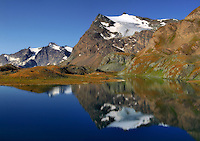Punta Basei, one of the many peak of the Gran Paradiso massif, reflected in the waters of Leità Lake, in the heart of the Gran Paradiso National Park in Piedmont, Italy. Taken an early morning of mid August, this is stitched from four vertical frames.