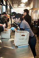 Employees hustle to fill and serve orders at the grand opening of the Shake Shack in Downtown Brooklyn in New York on Tuesday, December 20 2011. The popular restaurant, run by noted chef Danny Meyer's Union Square Hospitality Group, opens its first Brooklyn branch adding the location to the other branches in New York, Miami, Connecticut, Washington, DC and Dubai. The restaurant worked with the NYC Workforce1 Career Centers to hire 50 employees. (© Richard B. Levine)