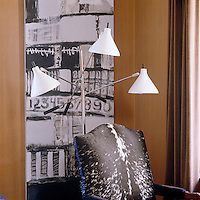 In the study an armchair covered in black-and-white cowhide co-ordinates with the abstract painting behind and a three-pronged reading lamp provides ample light