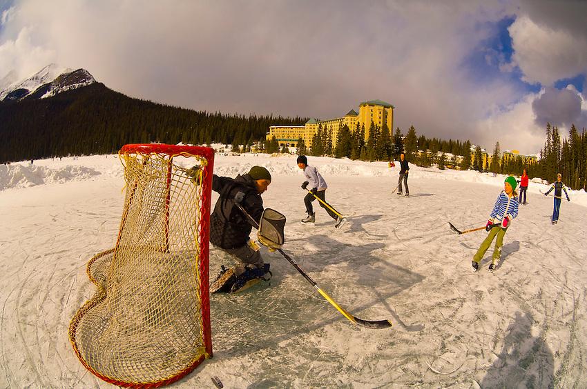 Playing hockey on Lake Louise, near the Fairmont Chateau Lake Louise Hotel, Banff National Park, Alberta, Canada