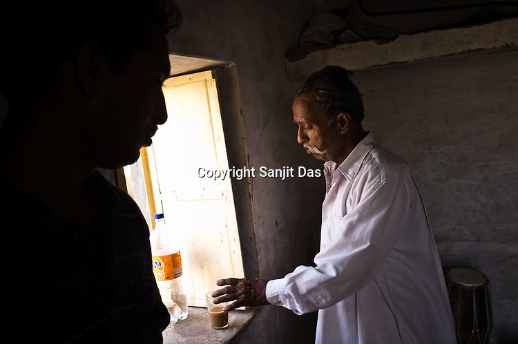 66-year-old Manganiyar artist, Lakha Khan drinks tea before sitting down for field recording of his Sarangi performance in his house in Raneri village of Jodhpur district in Rajasthan, India. Photo: Sanjit Das/Panos