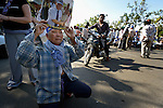 """A man kneels as he participates in a vigil outside a Phnom Penh court on December 14, 2012, during a hearing in which judges denied an appeal by Mam Sonando, a Cambodian radio journalist and human rights activist. Mam Sonando was sentenced in October 2012 to 20 years in prison for """"insurrection,"""" despite local and international calls for his release."""