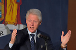 Elmont, New York, USA. April 5, 2016. Former President Bill Clinton, raising his hands up in wide open gesture, is the headline speaker as he campaigns at an Organizing Event rally in Elmont, Long Island, on behalf of his wife, Hillary Clinton, the leading Democratic presidential candidate, and former Secretary of State and U.S. Senator for New York. Podium has 'Fighting for us' slogan on sign. The New York Democratic Primary takes place April 19th.