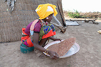Girl shaking and holding a tray of Sorghum for use in the preparation of Injerra, a sort of pancake made of Teff, Northern Ethiopia.