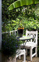 The terrace is furnished with a pair of wooden garden chairs and an inlaid mosaic table with a miniature orange tree