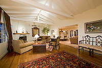 Spanish family room featuring white painted bemed cielings, elegant furnishings, hardwood floors and large windows.