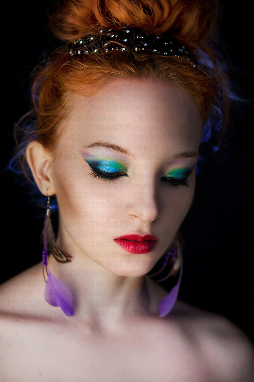 redhead with colourful makeup, looking down