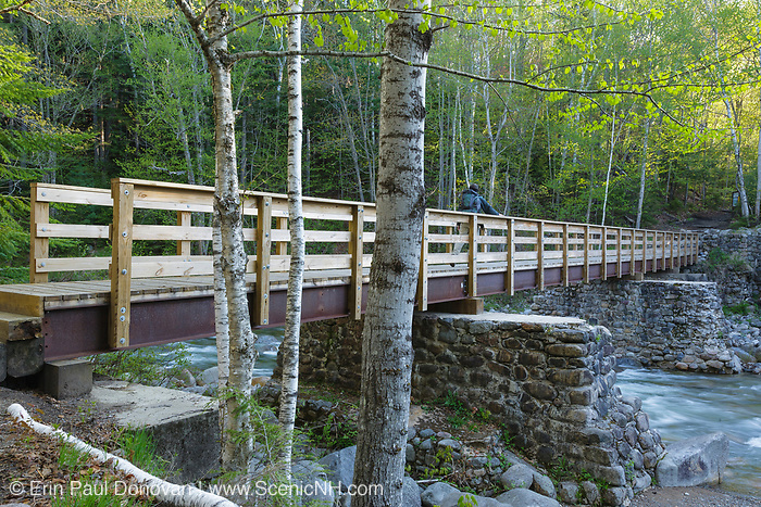 A hiker crosses over Franconia Brook on a foot bridge in Lincoln, New Hampshire. Old abutments from Trestle 7 of the old the East Branch & Lincoln Logging Railroad are used to support the foot bridge. The East Branch & Lincoln Railroad operated from 1893 - 1948.