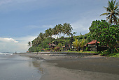 Looking along the beach in front of the Rambut Siwi sea temple in Bali, Indonesia.