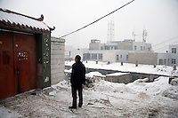 A man waits at a door outside a house in a Han neighborhood in Urumqi, Xinjiang, China. The city is divided between Han and Uighur ethnicities, and violent clashes erupted between the groups in 2009.