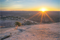 From the top of Enchanted Rock, the sun breaks over the horizon in the distant hills on a cold February morning.