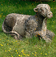A weathered stone sculpture of a calf nestles in the grass which is scattered with buttercups
