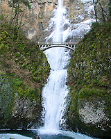 Multnomah Falls iced over in winter with river frozen below and bridge going across the icy falls.  Moss covered rocks are also seen.