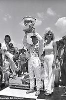 Gordon Johncock lifts the trophy after winning a 1976 USAC Champ Car race at Michigan International Speedway near Brooklyn, Michigan, USA.