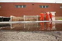 Inmates Samuel Soto, Shawn O'Hanlon, and E'Ton Littlepage inspect the ventilated thirty-day compost pile outside of the old Holmesburg Prison. After thirty days, the inmates move the compost to another pile where it remains for ninety days.