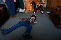 Dressed as a cowboy, Sheriff Tanner Lauman is &quot;shot dead&quot; on the living room floor in a moment of play.<br /> <br /> Kitty Lauman trains mustangs--as she says working with the horses, not against them.  They have a ranch in Prineville, OR.<br /> <br /> Kitty, her husband Rick and their children, Josie, 2 &frac12;,  and Tanner, 5,  ride mustangs. Kitty Lauman started her career as a horse trainer at the tender age of nine, under the guidance of her grandfather, John Sharp. <br /> <br /> She later became a top Pee Wee and High School Rodeo contestant, competing in barrel racing and cutting, among other events. Despite her mother's assertion that &quot;horse training isn't a real job,&quot; Kitty managed to make a living as a trainer after high school (and her mom now helps out with the business!) <br /> <br /> Kitty won the title of Miss Rodeo Oregon in 1994, and since then, has continued to expand her horse training knowledge and experience.  She placed second in the Extreme Mustang Makeover, a national competition in 2008.