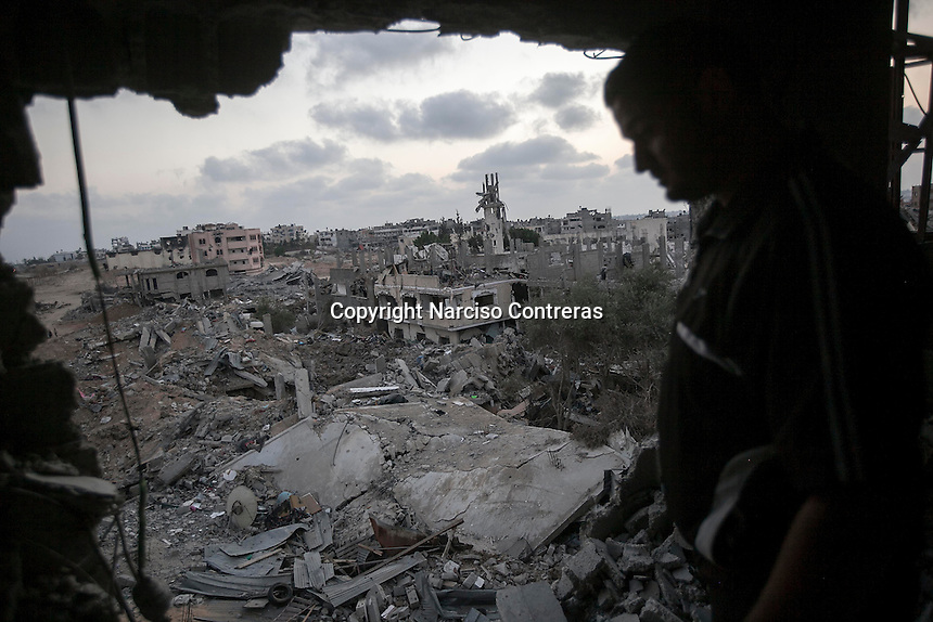 """In this Sunday, Aug. 17, 2014 photo, a Palestinian man looks for his belongings among the rubble of his house destroyed by israeli airstrikes and artillery shelling during the """"Protective Edge"""" military operation in Shuyaja neighborhood in Gaza City. After a five days truce was declared on 13th August between Hamas and Israel, civilian population went back to what remains from their houses and goods in Gaza Strip. (Photo/Narciso Contreras)"""