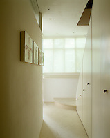 The walls, carpets and painted understairs cupboard are all white and a window blind creates a diffused light in this tranquil entrance hall