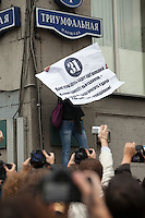 Moscow, Russia, 31/08/2010..A demonstrator waves a poster with article 31 of the Russian Constitution as police break up an opposition protest in central Moscow and arrest around 70 people. Opposition activists hold regular demonstrations on the 31st day of the month, protesting against restrictions on the freedom of assembly, which is protected by article number 31 of the Russian constitution.