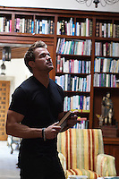man holding a book while looking around his home library