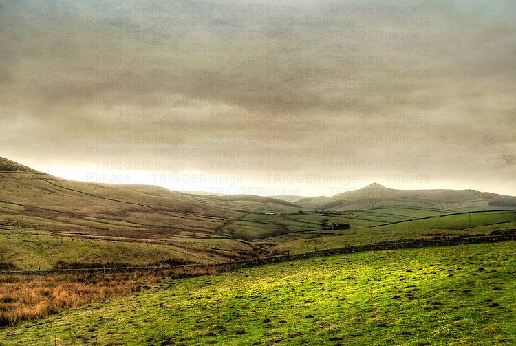 Rolling landscape with fields and pastures under grey sky