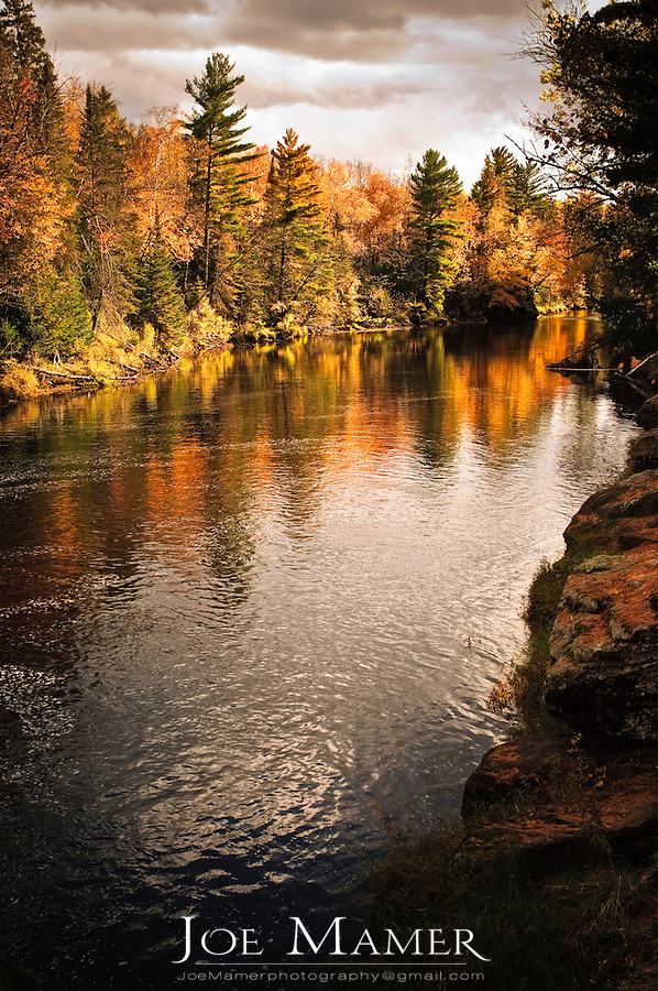 Colorful fall foliage along the Kettle River flowing through Banning State Park in autumn. Banning State Park is near Sandstone, Minnesota.