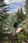 A backpacker walking across a footbridge in  the Bob Marshall Wilderness in Montana