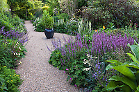 Gravel path between double perennial border with urn focal point; Gary Ratway garden