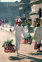Nepalese man carrying vegetables in hanging baskets through the streets of Patan, Nepal. RESERVED USE - NOT FOR DOWNLOAD -  FOR USE CONTACT TIM GRAHAM