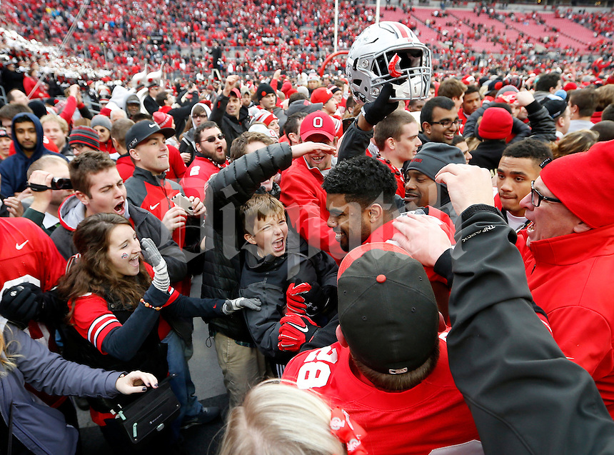 Fans high five Ohio State Buckeyes running back Ezekiel Elliott (15) as he leaves the field following the NCAA football game against the Michigan Wolverines at Ohio Stadium on Nov. 29, 2014. The Buckeyes won 42-28. (Adam Cairns / The Columbus Dispatch)