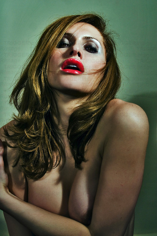 A naked young woman with red lipstick and long hair