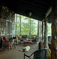 This rustic porch is furnished with a collection of wicker chairs and benches
