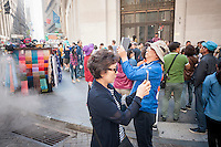 Asian tourists on Wall Street in New York on Friday, October 7, 2016 take photographs with their smartphones. (© Richard B. Levine)
