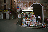"April 27, 1990, Rome, Italy. Photographing for the book ""One day in the life of Italy"", this is an exploration of Rome. In Lungotevere the newspaper stand opens at 5am and the newspaper street vendor sells directly to car drivers."