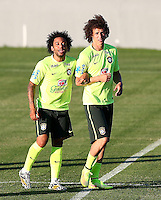 Marcelo and David Luiz of Brazil link arms as they joke around during training ahead of tomorrow's World Cup quarter final vs Colombia tomorrow