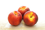 Group of three fresh orgaic peaches on marble table - fading to white at top.