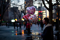 New York, United States. 14th February 2013 -- A woman waits for her lover as she carries globes as a present during celebrations of Saint Valentine's day in New York. Photo by Eduardo Munoz Alvarez / VIEWpress.