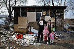 Vita Stankovic and his wife Arbanac Sofija, along with their daughters Rada, 5, and Caka, 3, stand in early 2012 outside their meager home in an illegal Roma settlement in Belgrade, Serbia. In February 2012, the family received the letter that Stankovic is holding informing them they will be evicted by city officials in March 2012 to make way for new high-rise office buildings.  In April 2012, the Serbian Orthodox family was forcibly evicted from the city center and given a metal shipping container in Makis, at the edge of Belgrade, where they could live. After several weeks, they were evicted from the shipping container because of Stankovic's repeated fights with his neighbors, and at the end of 2012 lived in an informal Roma squatter settlement in nearby Palilula. In 2009, they had been evicted from another settlement in Belgrade..