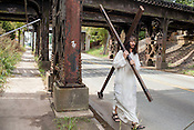 Dean crosses under the rusty rail bridge along Alston Avenue in East Durham. His cross, made from hardware store lumber, weighs nearly 40 pounds. The first time he carried it he described it as feeling like a boulder on his shoulder.
