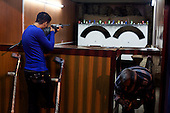 BAGHDAD, IRAQ: Hussein shoots bottles with an air rifle at an amusement park in central Baghdad...On January 22nd, 2012, an IED (Improvised Explosive Devise) detonated near an Iraqi Army base in Fallujah. Hussein Jamil Abdullah, a 28 year-old soldier from Baghdad was nearby when the explosive discharged, knocking him to the ground. Hey lay there for half an hour, his right leg in an jerry-rigged tourniquet made from a headscarf, before he was taken to hospital...Gangrene set in almost immediately and the doctors at Fallujah General Hospital had to amputate his leg. He was then moved to Adnan Hospital, the military medical center, but the care Hussein received was terrible. His bandage wasn'.t changed for two days and fearing that gangrene would set in a second time his family moved him to Kerkh Hospital, which they had to cover the costs themselves, as the army refused to pay...As soon as he was wounded, the Army cut Hussein.s salary in half: from $500 a month to $250, which is less than he can live on. His brother, Ali, has given up his work as a barber to take care of him, and his two other brothers, Abbas and Hassan, now take care of the family...Before he was wounded, Hussein, was to be engaged to his fianc&eacute;e, Hind and he had even bought and furnished a room in preparation. But, after the explosion, Hind.'s father refused to allow them to marry, saying that they can.t do so until Hussein gets a prosthetic leg...In the summer, a selection of photographs were published online and caught the attention of an NGO worker in Baghdad who arranged for Hussein to have a prosthetic leg fitted...Once he had his prosthetic leg, Hussein married Hind.