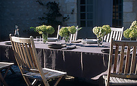 Makeshift glass vases are filled with flowers cut from the garden on this table laid with taupe table linen and simple crockery