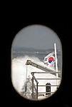 The Korean flag is seen through the window of a ferry as it sets off for Dokdo Island, South Korea on 22 June 2010..Photographer: Robert Gilhooly