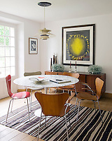 In the dining room a Saarinen Tulip table is surrounded by Arne Jacobsen 3107 chairs, with a colourful lithograph on the wall