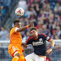 Houston Dynamo forward Giles Barnes (23) and New England Revolution midfielder Andy Dorman (12) battle for the ball.  In a Major League Soccer (MLS) match, the New England Revolution (blue/white) defeated Houston Dynamo (orange), 2-0, at Gillette Stadium on April 12, 2014.