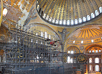 Scaffolding inside Hagia Sophia, erected to aid restoration of the dome, Istanbul, Turkey. Hagia Sophia, The Church of the Holy Wisdom, has been a Byzantine church, an Ottoman mosque and is now a museum. The current building, the third on the site, was commissioned by Emperor Justinian I and is a very fine example of Byzantine architecture. It was built 532-37 by Isidore of Miletus and Anthemius of Tralles. Picture by Manuel Cohen