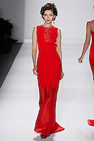 Model walks runway in a ruby silk crepe+organza princess gown w/ruby crystal beaded imperial frame necklace, from the Zang Toi Fall 2012 &quot;Glamour At Gstaad&quot; collection, during Mercedes-Benz Fashion Week New York Fall 2012 at Lincoln Center.