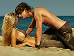 Sensual portrait of a young couple on the beach lying on sand