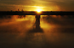 Photograph of a bridge over a foggy lake at sunrise with the sun just peeking over the center column