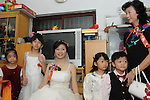 Taiwanese Wedding -- The bride at her home, surrounded by flower girls and boys, brimming with anticipation.